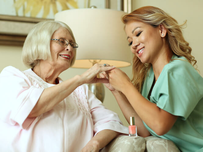 a female CNA helps with nail care for a senior woman resident