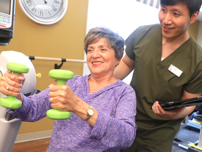 male senior fitness instructor assists senior female resident