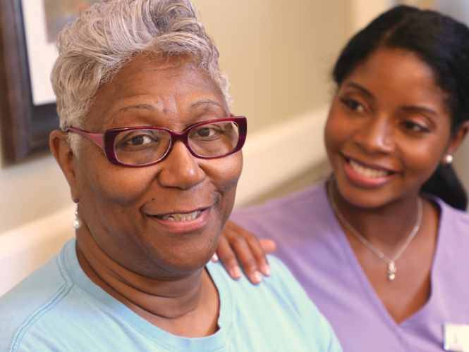 a female respite care staff smiles with older adult female