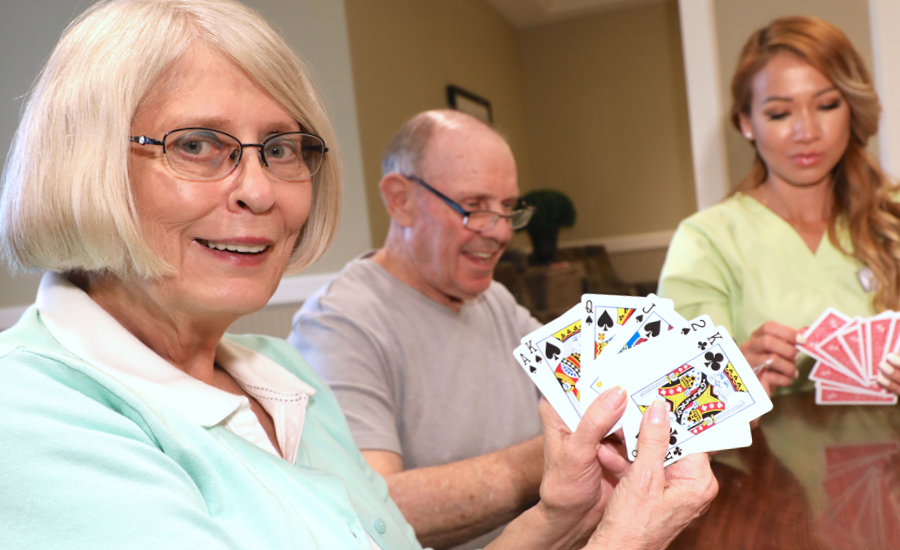 a senior woman plays cards with friends