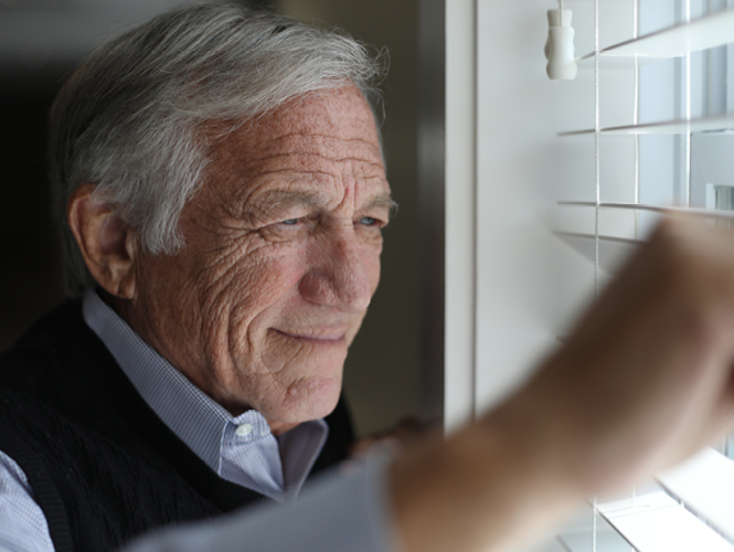 older adult male looks out window pensively