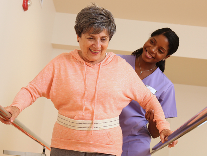 female therapist assists female rehab patient with gait belt