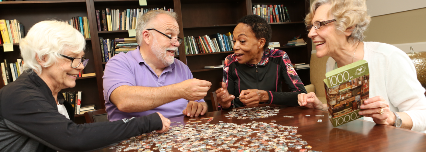 A group of friends work on a jigsaw puzzle at Village Woods Senior Living Community