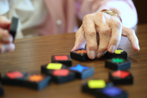close up of senior female's hands moving pieces of memory care activity