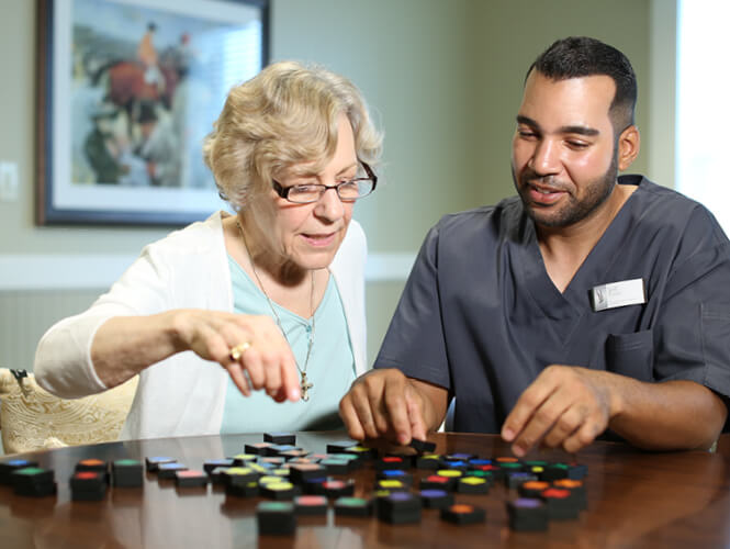an older woman and a male worker playing a board game in memory care
