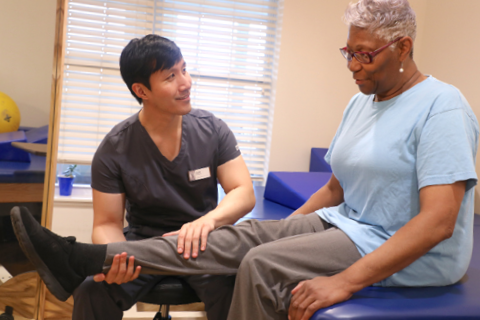 male therapist assists senior female with rehab exercise