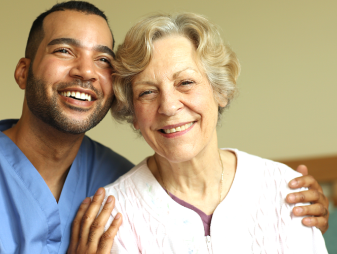 Male home healthcare worker smiles with senior woman