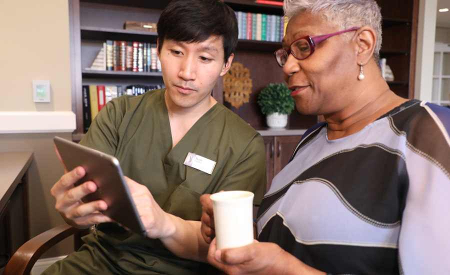 male healthcare manager uses iPad to discuss treatment plan with senior woman