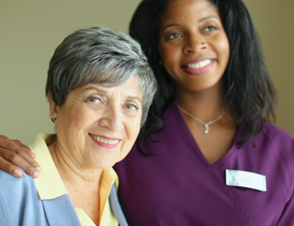 older adult female respite client smiles with her female CNA