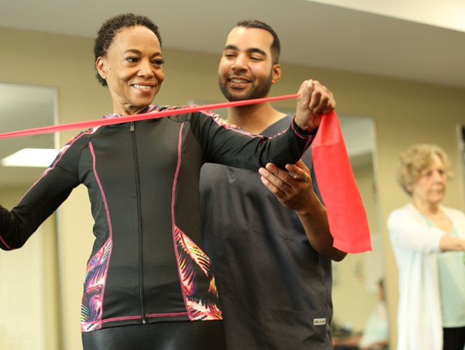male senior fitness instructor assists female resident with exercise bands