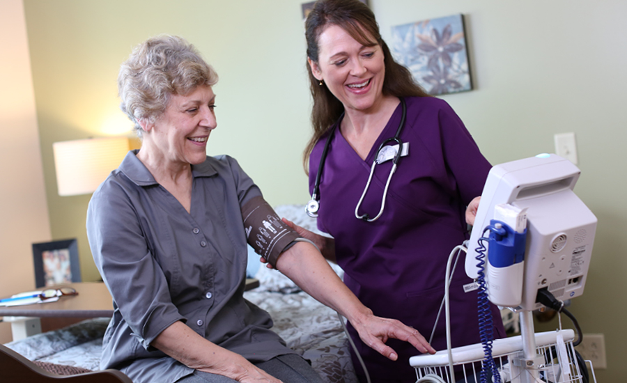 female healthcare staff takes providence resident's vitals