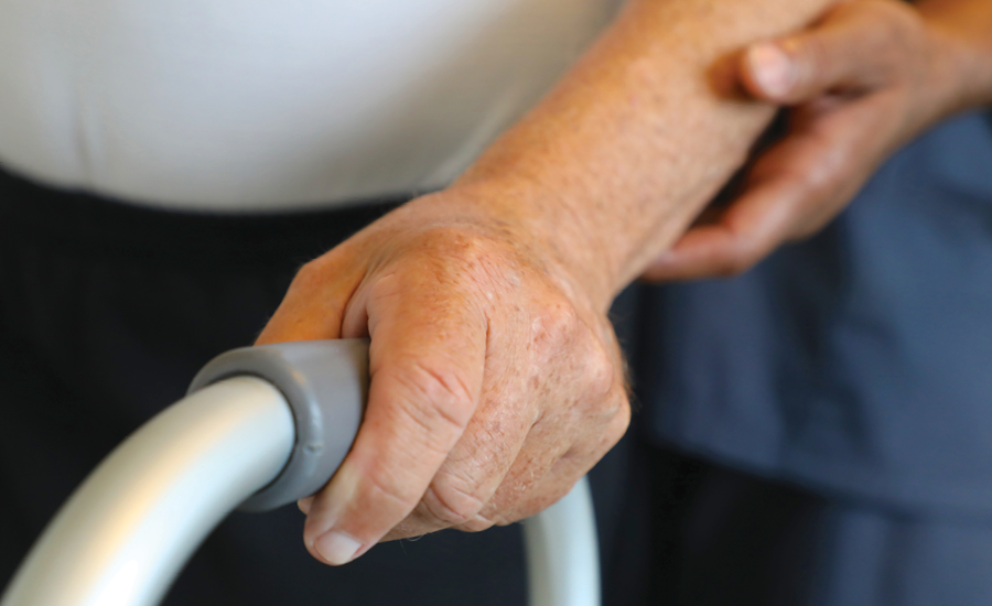 close up of hand-over-hand guiding using a walker