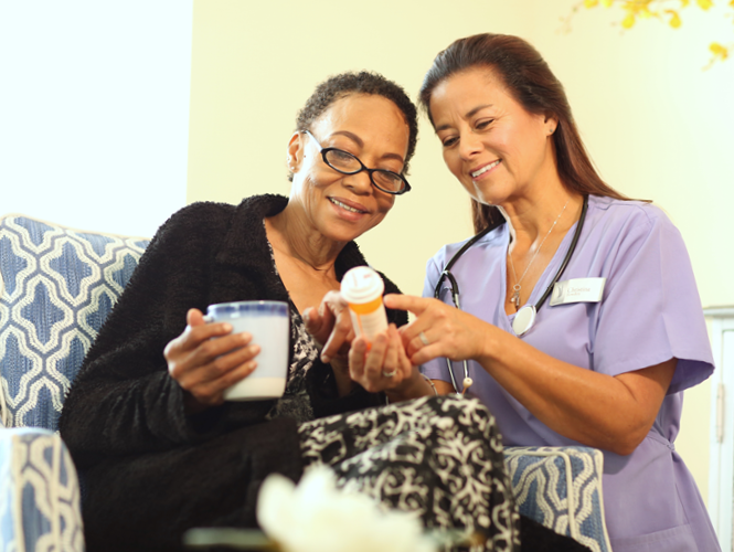 senior woman holds coffee mug as hospice worker explains treatment plan