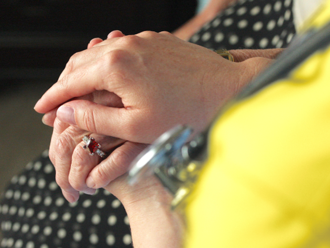 the hand of a providence hospice worker comforts the hand of a hospice patient