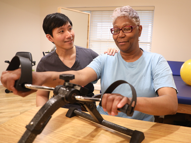 a male cna helps senior woman on exercise bike