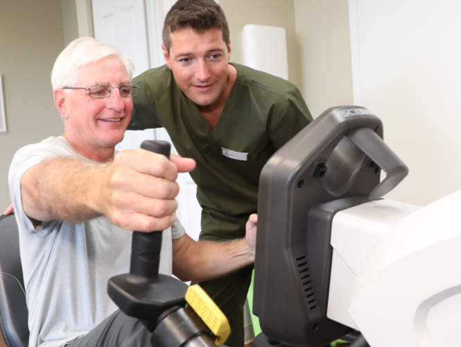 male senior fitness instructor assists male resident on exercise bike