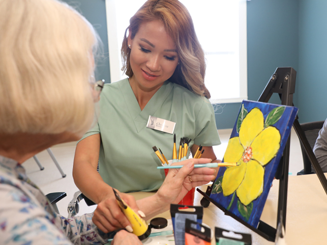 a cna assists an emerald meadows resident on an art project