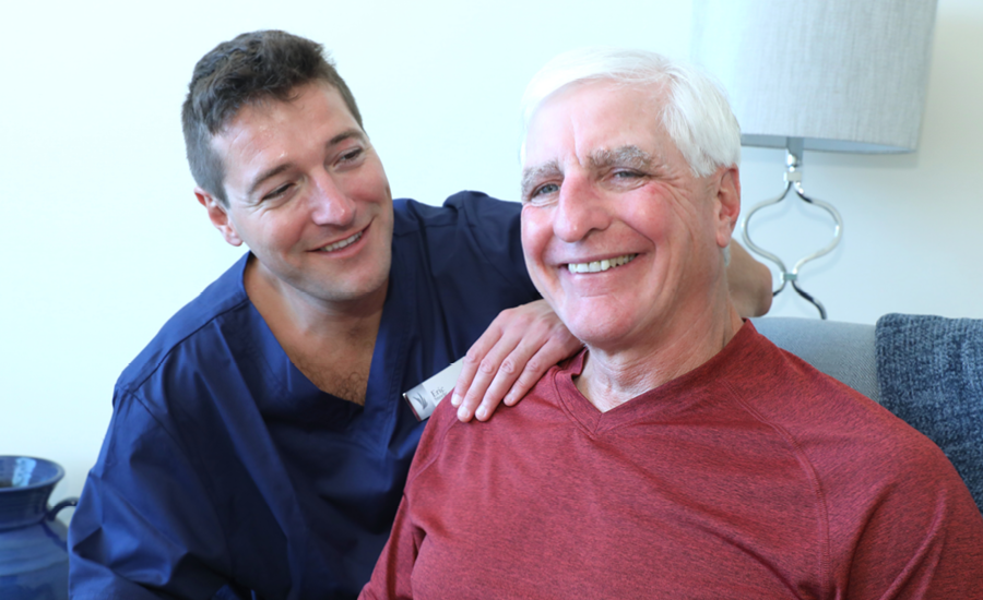 male CNA assists older adult male