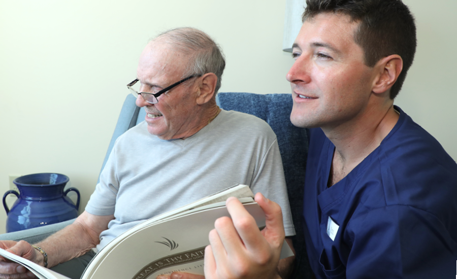providence hospice cna discusses palliative care plan to senior male patient