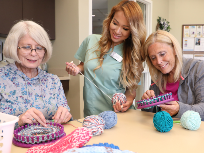 two senior residents and a volunteer make hats on a loom