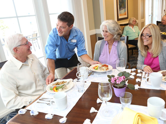 a man serving lunch to an older man and two older women