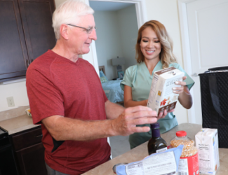 A CNA assists respite client with breakfast