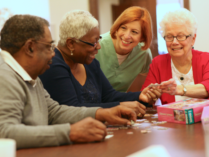 female cna helps three senior residents play game