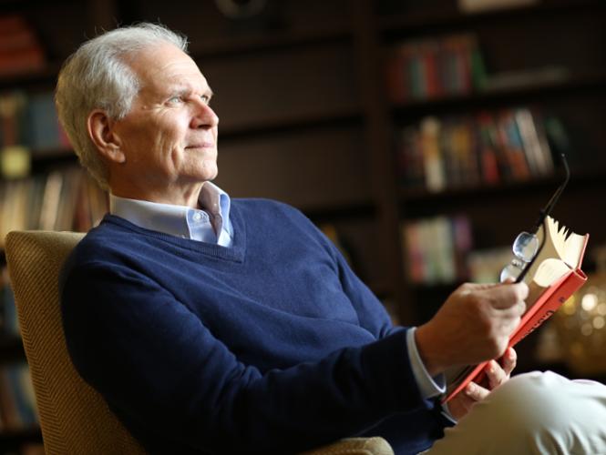 senior male resident attends spiritual service holding bible