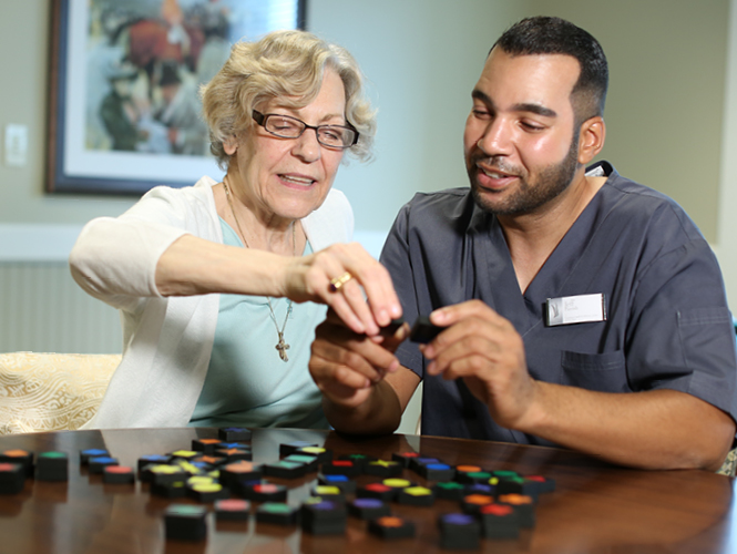 emerald meadows resident completes activity with her cna in memory care