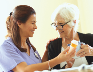 female CNA helps senior woman understand medication