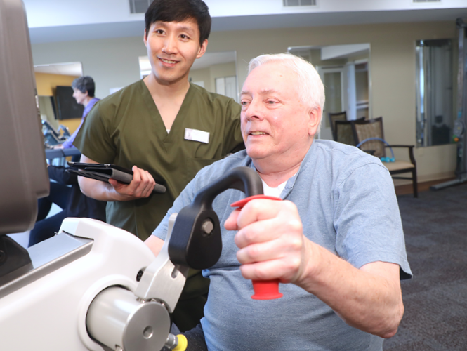 a male CNA assists male resident on exercise bike