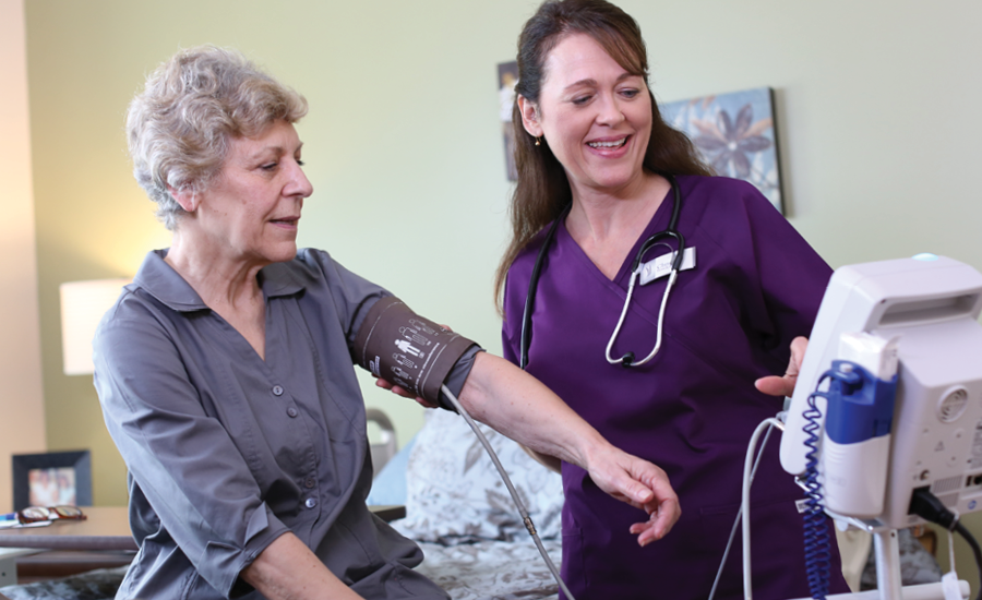 cna takes vital signs of female nursing home resident