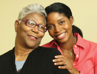 an older adult female and her female CNA smile together
