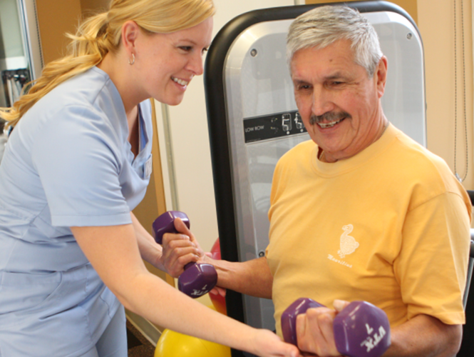 a senior fitness instructor assists male resident in gym