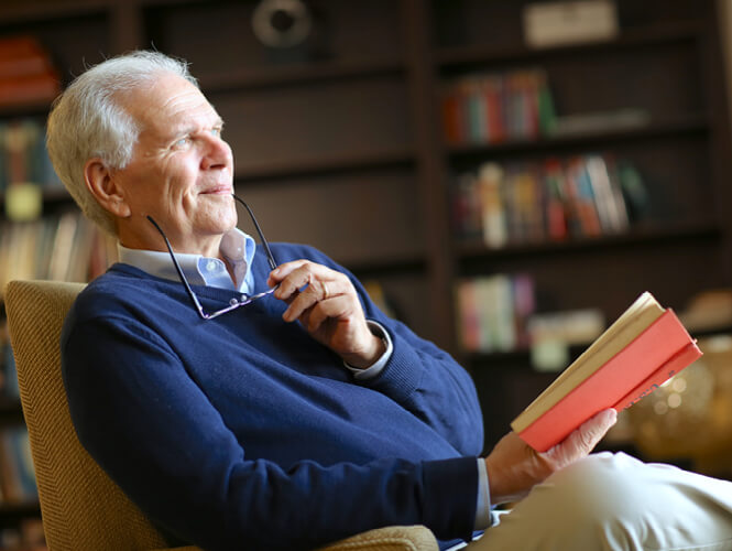 an older man in the study reading a book