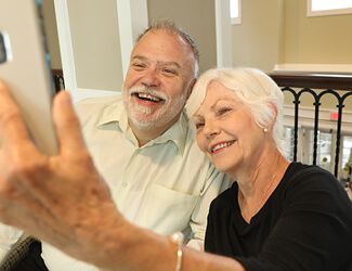 a senior couple takes a selfie enjoying independent living at victorian village