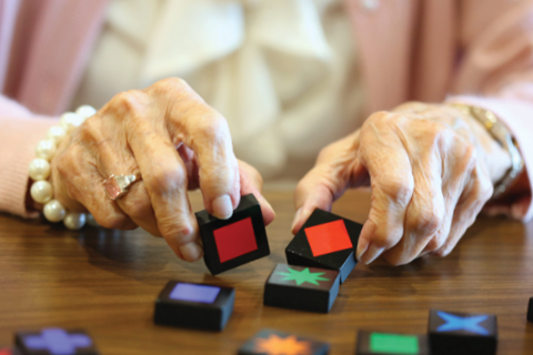 close-up of female's hands completing memory care activity