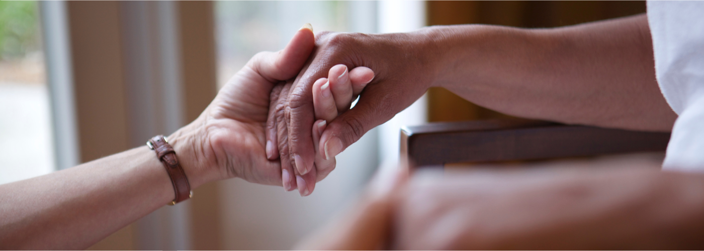 Providence hospice worker;s hand holds a hospice patient's hand
