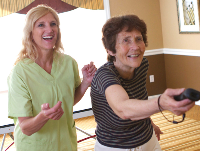 female resident aide assists senior female resident with wii bowling