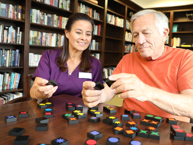 female cna works on puzzle with male memory care resident