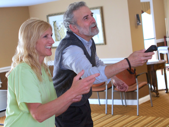 life enrichment staff assists male resident with wii bowling