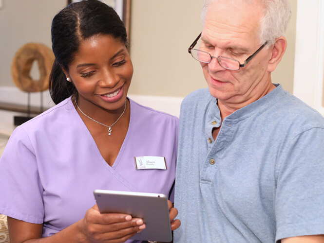 a female CNA showing an elderly man care plan on an ipad