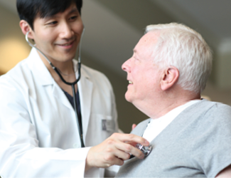 A male doctor takes senior male resident's vitals