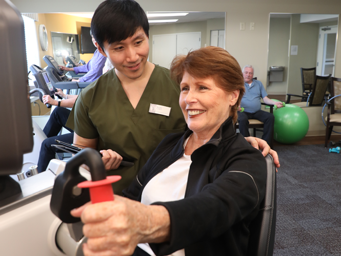 an elderly woman riding an exercise bike as male cna assists