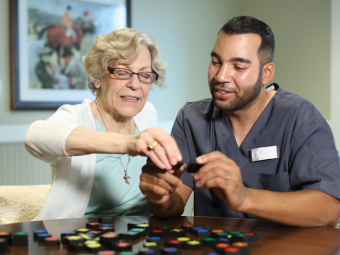 a female older adult and a male staff complete memory care activity
