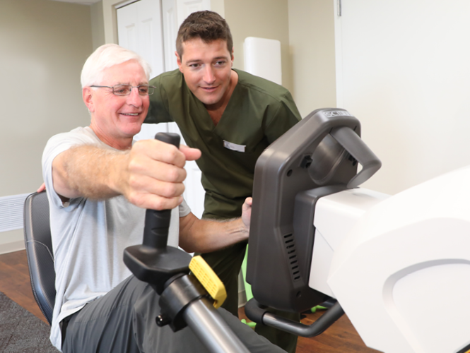 male CNA assists older adult male on exercise bike