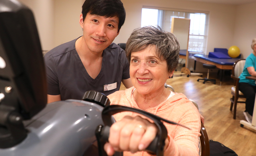 male staff helping satisfied resident on exercise bike