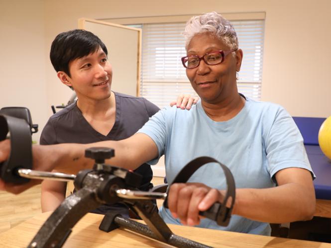 a male CNA assist a senior female rehab patient