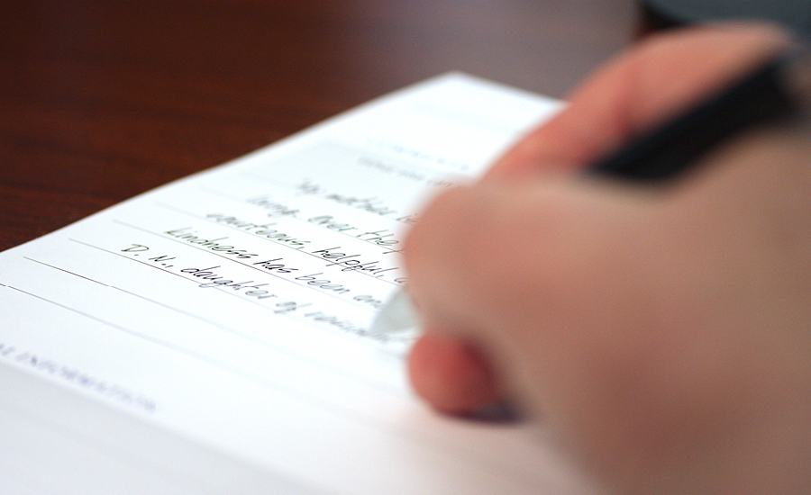 Hand writing emerald meadows testimonial on paper