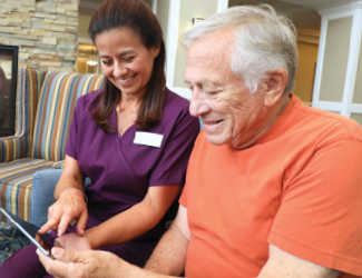 picture of providence solutions caregiver helping senior man understand his benefits